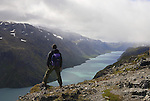 Man overlooking Lake Gjende during the famous walk Besseggen in Jotunheimen mountain range in Norway