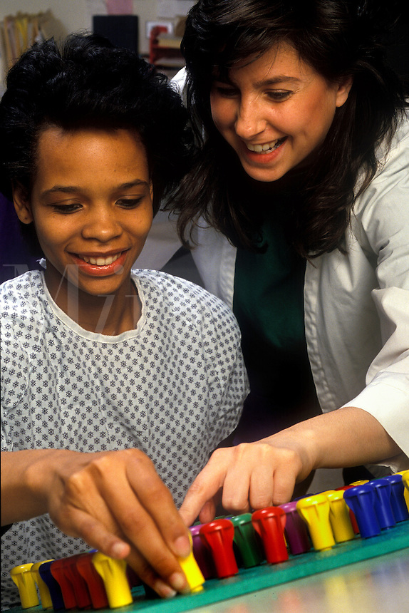 Physical therapist with patient working on motor skills at a peg board.