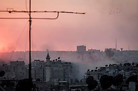 The sun sets up at the sunset as smoke rises from a mortar explosion over the Arkup district where the heavy fighting and shelling have taken place during the battle in the last week between rebel forces and Syrian army for the control of Aleppo City.