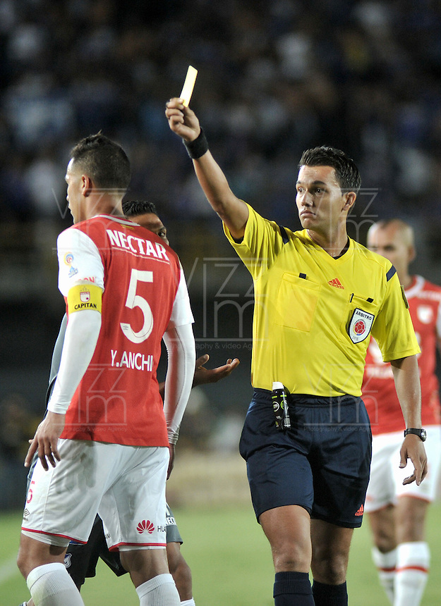 BOGOTA - COLOMBIA - 07-02-2016: Nicolas Gallo, arbitro, muestra tarjeta amarilla a Yulian Anchico, jugador de Independiente Santa Fe, durante partido por la fecha 2 entre Independiente Santa Fe y Millonarios de la Liga Aguila I-2016, en el estadio Nemesio Camacho El Campin de la ciudad de Bogota. / Nicolas Gallo, referee, shows yellow card to Yulian Anchico, player of Independiente Santa Fe, during a match of the 2 date between Independiente Santa Fe and Millonarios, for the Liga Aguila I -2016 at the Nemesio Camacho El Campin Stadium in Bogota city, Photo: VizzorImage / Luis Ramirez / Staff.
