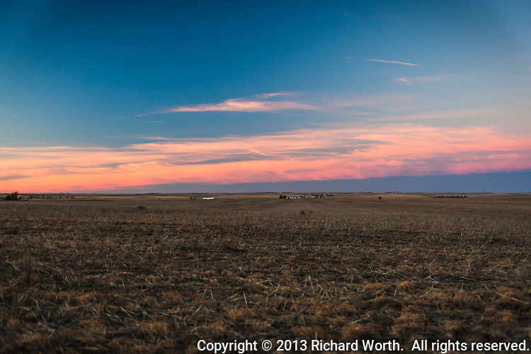 A farmhouse and out buildings behind a recently harvested field with sunset's glow on the distant horizon.  Otis. Colorado.