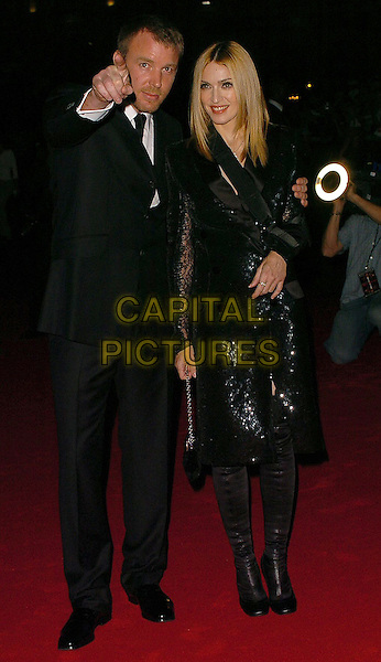 "GUY RITCHIE & MADONNA.Arrivals at The ""Revolver"" world premiere held at The Odeon Cinema, Leicester Square,.London, 20th September 2005.full length black jacket coat knee boots suit pointing point finger hand.Ref: CAN.www.capitalpictures.com.sales@capitalpictures.com.©Capital Pictures"