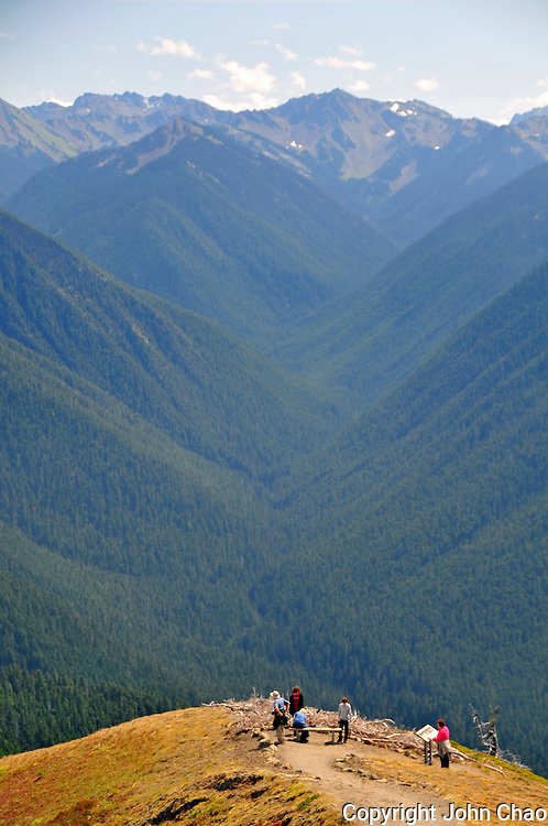 Vertical image of tourists at a high ridge viewpoint in the Hurricane Ridge area, Olympic National Park.