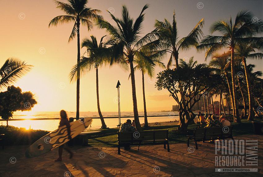 Surfer, beach goers, tourists walking along the sidewalk at Kuhio Beach in Waikiki, Honolulu, Oahu.