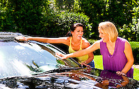 Girlfriends having fun washing car at home and relaxing together