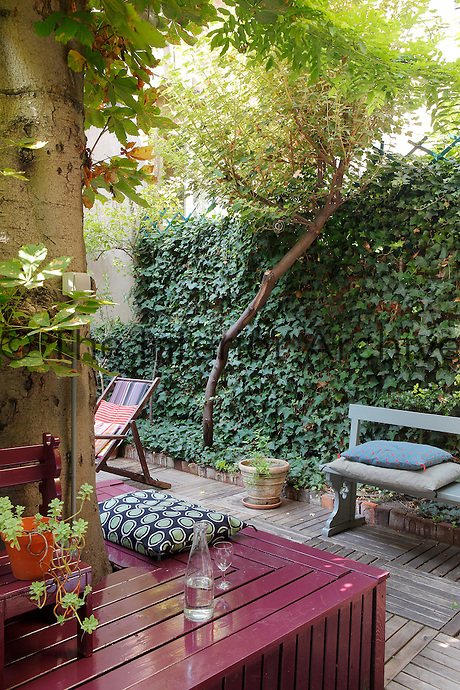 The chestnut tree in the centre of the courtyard has been encased with a painted wooden seat and the surrounding garden laid with decking