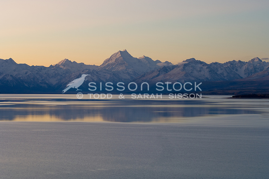 Aoraki Mount cook is reflected in lake pukaki after sunset.  The southern alps are fully visible..