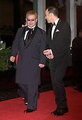 "2004 Kennedy Center Honoree Sir Elton John arrives with David Furnish at the Harry S. Truman Building (Department of State) in Washington, D.C. on December 4, 2004 for a dinner hosted by United States Secretary of State Colin Powell.  At the dinner six performing arts legends will receive the Kennedy Center Honors of 2004.  This is the 27th year that the honors have been bestowed on ""extraordinary individuals whose unique and abundant artistry has contributed significantly to the cultural life of our nation and the world"" said John F. Kennedy Center for the Performing Arts Chairman Stephen A. Schwarzman.  The award recipients are: actor, director, producer, and writer Warren Beatty; husband-and-wife actors, writers and producers Ossie Davis and Ruby Dee; singer and composer Elton John; soprano Joan Sutherland; and composer and conductor John Williams..Credit: Ron Sachs / CNP"