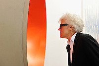 HONG KONG - MARCH 13:  A visitor looks at sculpture 'Monochrome (Neon Orange)' by Anish Kapoor on the preview day of Art Basel art fair on March 13, 2015 in Hong Kong, Hong Kong.  (Photo by Lucas Schifres/Getty Images)