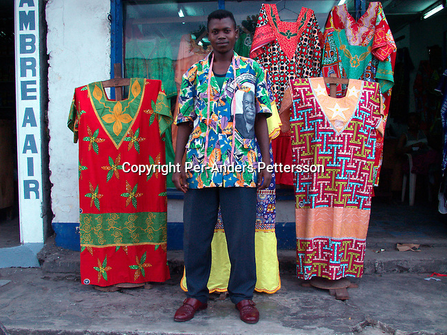 dicocon00171.Congo. Kinshasa. Business. Retail, Traditional dresses. Sylla Amara, a tailor outside his shop (called Mandino) with his work on February 28, 2002 in a busy street in central Kinshasa, Congo.  The shirts are typical Congolese, but also makes West African shirts for clients. Especially women come to buy his clothes and his clientele includes people from Zimbabwe, Mali and Togo measure lint..©Per-Anders Pettersson/iAfrika Photos