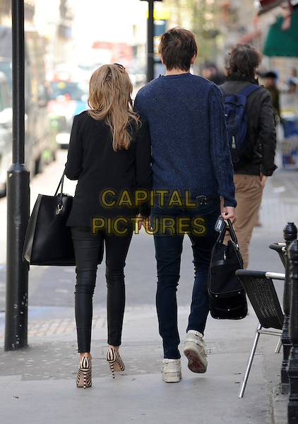 Tom Kilbey & Lydia Rose Bright .Spotted in London, England..March 12th, 2013.full length black blue sweater jumper top jeans denim holding hands blazer bag purse stripe shoes couple back behind rear     .CAP/AOU.©AOU/Capital Pictures.