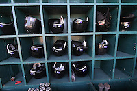 black Colorado Rockies baseball helmets on green wooden rack
