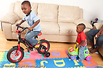12 month old baby boy on wheeled plastic toy looking at his 3 year old brother on his bicycle with training wheels horizontal