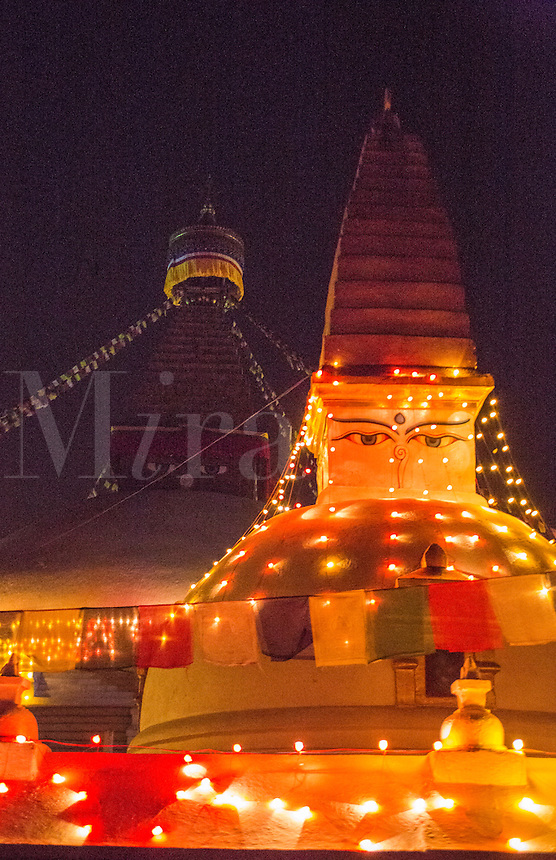 Kathmandu Nepal Boudhanath Stupa partially lit by colorful lights in the early morning.