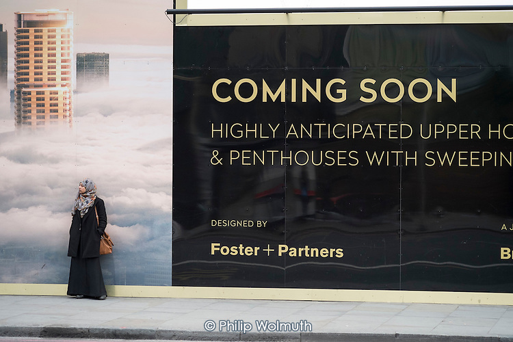 Woman waiting for a bus by a hoarding advertising new luxury housing in Shoreditch, London.