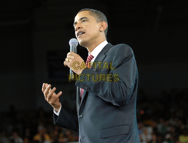 BARACK OBAMA .Senator Barack Obama speaks at the Minges Coliseum as he campaigns for a Presidential bid..Greenville, North Carolina, USA,.17 April 2008.half length microphone suit jacket red tie politics presidential campaign rally .CAP/ADM/MOO.©Moose/Admedia/Capital Pictures