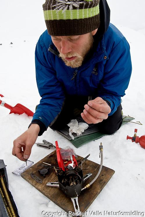 Mann vedlikeholder primus. ---- Man maintaining stove.