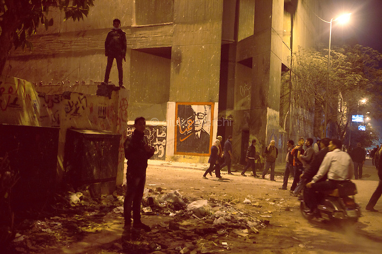 EGYPT / Cairo / 27.11.2012 / Young protesters on a wall in Mohamed Mahmoud Street just nearby Tahrir square, where thousands of people have gathered to protest President Morsy's above-the-law constitutional declaration. <br /> <br /> © Giulia Marchi