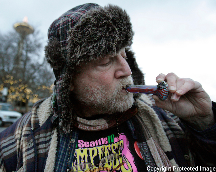 Michael Dare, a medical marijuana user, smokes a pip full of bud at a  public consumption of marijuana at the Seattle Center on December 6, 2012 in Seattle. Despite the new law's ban on public marijuana use which is subject to a fine of about $50.00 many showed up for the smoke in. In November Washington jumped into history becoming the first state along with Colorado to reject federal drug-control policy and legalize recreational marijuana use.    ©2012. Jim Bryant Photo. All Rights Reserved.