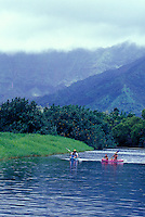 Family with mother, father, son and daughter paddling kayaks on the Hanalei River with waterfall of Mount Waialeale in background, Kauai, Hawaii
