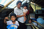 VOLCANO AFTERMATH, Philippines. Family living in tent, single parent   with 3 children, eating. Central Luzon, Mount Pinatubo volcano erupted in 1991  and caused massive destruction of urban and rural landscape. Many indigenous  Aeta and Igorot people were displaced. White volcanic  ashes settled and disfigured the landscape.   Many  live in ramshackle shelters, in  refugee camps and settlements, living on humanitarian aid.