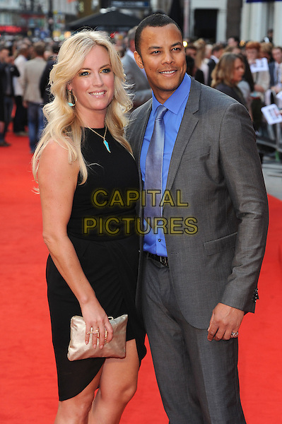 guest & Michael Wildman.'The Sweeney' European film premiere, Vue West End cinema, Leicester Square, London, England..September 3rd, 2012.half 3/4 length suit black dress clutch bag gold blue shirt grey gray tie.CAP/BEL.©Tom Belcher/Capital Pictures.