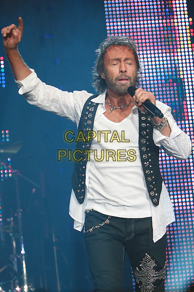 BAD COMPANY - Paul Rogers.Performing live at Wembley Arena, London, England..April 11th, 2010.stage concert live gig performance music half 3/4 jeans denim white shirt waistcoat singing microphone beard length facial hair arm in air .CAP/MAR.© Martin Harris/Capital Pictures.