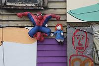 pupazzo uomo ragno e bambola appesa a una parete esterna di casa americana