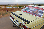 LEBANON Beqaa valley, Deir el Ahmad, camp for syrian refugees, old german Mercedes Benz car with german country code D , lebanese flag and image of Baalbek temple, background Anti Lebanon mountains and Syria / LIBANON Bekaa Tal, Deir el Ahmad, Camp fuer syrische Fluechtlinge am Dorfrand, alter Mercedes Benz mit D Laender Kennzeichen, libanesischer Flagge und Foto des Baalbek Tempels