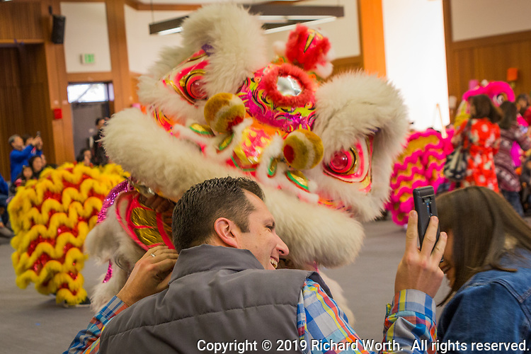 During the Lion Dance performance at the Lunar New Year celebration an audience member grabs a selfie with one of the lions.