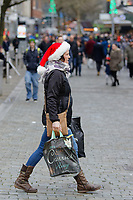 A last minute Christmas shopper with a Santa hat in Oxford Street, Swansea, Wales, UK. Monday 24 December 2018