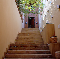 A flight of wooden steps leading to the entrance is lit at night by banks of small square wall lights