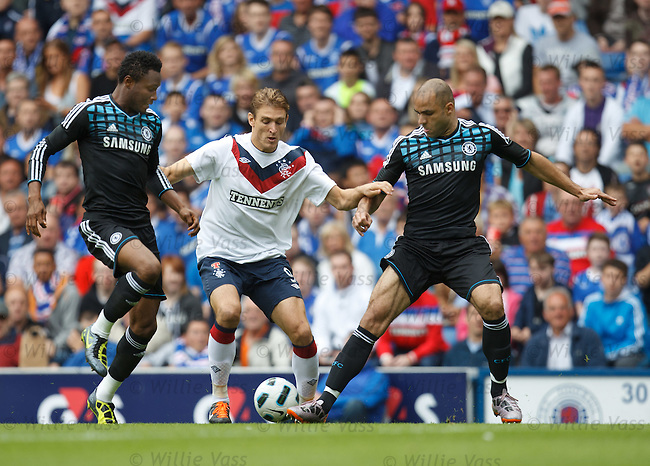 Nikica Jelavic squeezs past Chelsea duo John Obi Mikel and Alex