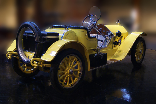 Bright yellow Stutz Bearcat with black leather seat and trim, yellow wheels photographed showing the rear and right side against a blurred background camouflaging the environment at J.K.Lilly III Antique Automoble Museum, Heritage Museum and Gardens, Sandwich, MA.