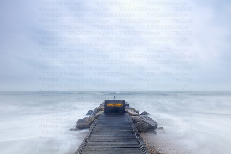 Stormy rough seascape with stone jetty
