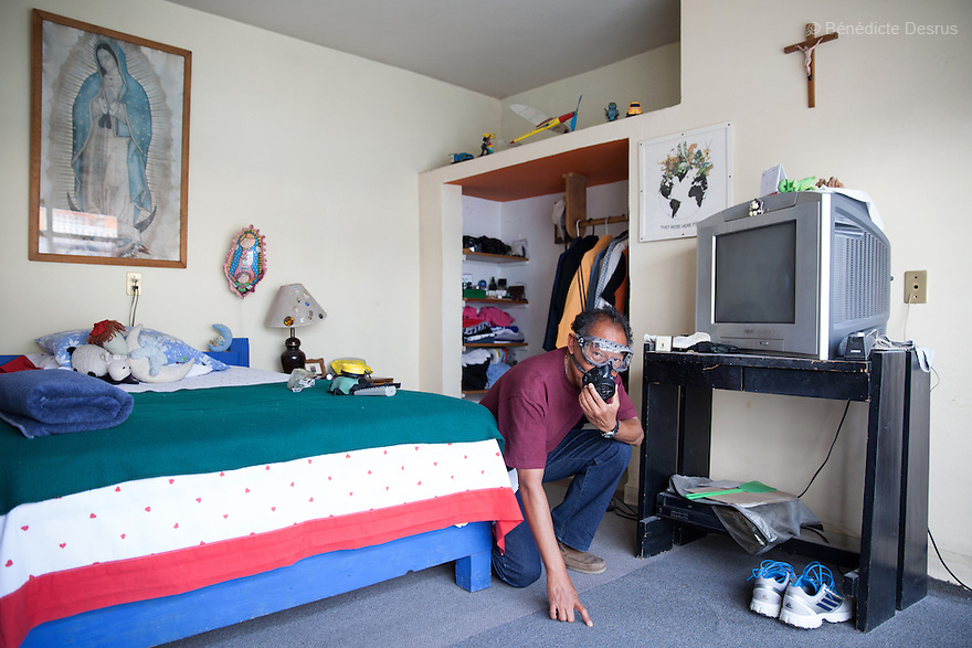 """Salvador Garcia Angeles portrayed in his bedroom in Azcapotzalco, Mexico on May 15, 2015. Salvador, 53, owns a stationery store in Mexico City, and has worked part-time for the past eight years as an assistant to his nephew, Donovan Tavera, a forensic cleaner. He says that his fastest cleaning –a suicide– took him 30 minutes to complete, and that his longest –a multiple homicide– took him eight hours. Donovan Tavera, 43, is the director of """"Limpieza Forense México"""", the country's first and so far the only government-accredited forensic cleaning company. Since 2000, Tavera, a self-taught forensic technician, and his family have offered services to clean up homicides, unattended death, suicides, the homes of compulsive hoarders and houses destroyed by fire or flooding. Despite rising violence that has left 70,000 people dead and 23,000 disappeared since 2006, Mexico has only one certified forensic cleaner. As a consequence, the biological hazards associated with crime scenes are going unchecked all around the country. Photo by Bénédicte Desrus"""