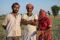 Guar farmer Bhanwarlal Sharma, 60, poses for a portrait with his wife, Mirga Devi, 58, and son, Arjun Sharma, 28, in his agriculture field in Bamanwali village, Bikaner, Rajasthan, India on October 24th, 2016. Non-profit organisation Technoserve works with farmers in Bikaner, providing technical support and training, causing increased yield from implementation of good agricultural practices as well as a switch to using better grains better suited to the given climate. Photograph by Suzanne Lee for Technoserve