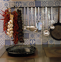 A wall of mismatched blue and white tiles supports a rail of stainless steel kitchen utensils, garlic and dried chillies