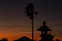 Silhouette of Mount Fuji seen behind a stone lantern and palm trees at sunset in Enoshima, Kanagawa, Japan. Monday October 23rd 2017