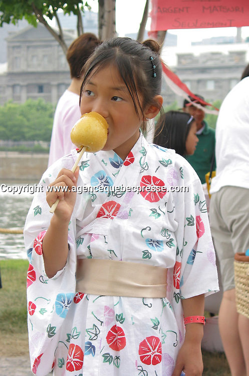 July 6  2002, Montreal, Quebec, Canada<br /> <br /> A Japanese young  girl dressed in a traditional kimono,<br /> enjoy a typical Japanese dessert made of a fruit coated with sugar, during the Matsuri one day Japanese Festival in Montreal Old Port, Juy 6 2002.<br /> <br /> The event feature demonstration of Japanese traditional martial art, music, food and other activities.<br /> <br /> <br /> <br /> Mandatory Credit: Photo by Pierre Roussel- Images Distribution. (&copy;) Copyright 2002 by Pierre Roussel <br /> <br /> NOTE :<br /> Canon G-2 oroginal jpeg, converted from sRG to  Adobe 1998 RGB.<br /> Original size and uncompressed file available on request.