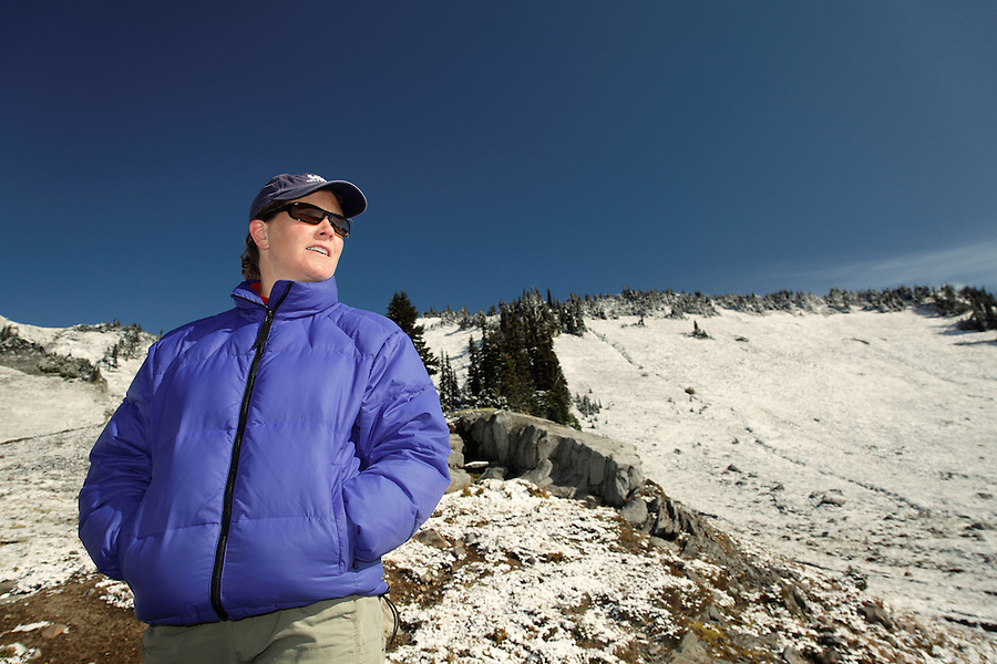 Woman hiker in snow dusted mountain landscape, Mount Rainier National Park, Washington, USA