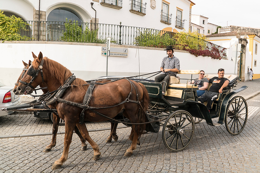 A horse-drawn carriage cares a couple through the streets of Évora, Portugal.