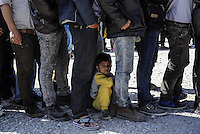 Pictured: A young boy rests on the ground amongst men who queue for food Friday 26 February 2016<br />