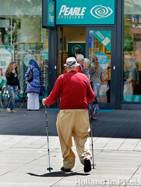Man loopt met nordic walking stokken bij een Pearle winkel in Eidhoven
