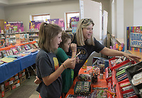 NWA Democrat-Gazette/CHARLIE KAIJO Eden Yingst, 13, Liliana Yingst, 9 and Carrie Yingst of Centerton look at bookmarks during the Scholastic Book Fair, Thursday, June 6, 2019 at the 21c Hotel in Bentonville<br />