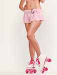 Sexy young woman wearing a pink mini skirt and classic retro roller skates isolated on off white background