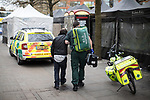 © Joel Goodman - 07973 332324 . 06/04/2017 . Manchester , UK . A paramedic tends to a man , believed to have taken spice in a telephone box . An epidemic of abuse of the drug spice by some of Manchester's homeless population , in plain sight , is causing users to experience psychosis and a zombie-like state and is daily being witnessed in the Piccadilly Gardens area of Manchester , drawing large resource from paramedic services in the city centre . Photo credit : Joel Goodman