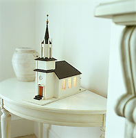 A musical box in the shape of a Swedish church lit from the inside sits on a semi-circular console table next to the fireplace