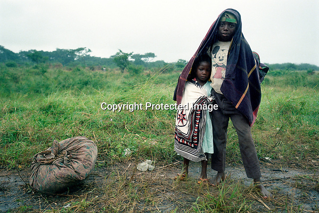 Two siblings wait for a lift during a heavy rainfall on March 7, 2000 along the main road in Chakuelane, Mozambique. The country was hit by severe floods in February-March 2000 that destroyed farmland, infrastructure and killed hundreds of people. (Photo by: Per-Anders Pettersson)