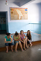 REPUBLIC OF MOLDOVA, Gagauzia, Vulcanesti, 2009/07/2..Students from Tomai hang in the hallways of the school. Courses are completed for a month. Tonight takes place the ceremony  of graduation..Behind them, a panel presents the Gagauzia, a small territory in southern Moldova. 90% of students are Gagauz, but classes are in Russian..© Bruno Cogez / Est&Ost Photography..REPUBLIQUE MOLDAVE, Gagaouzie, Tomai, 2/07/2009..Des élèves de Tomai trainent dans les couloirs de l'école. Les cours  sont terminés depuis un mois. Ce soir a lieu la cérémonie de remise des diplômes..Derrière elles, un panneau présente la Gagaouzie, petit territoire du sud de la Moldavie. 90% des élèves sont  Gagaouzes, mais les cours se font en russe..© Bruno Cogez / Est&Ost Photography